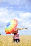 Romantisk kvinnlig med regnbågeparaplyet i vetet Fotografering för Bildbyråer