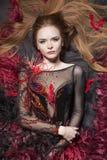 Romantisk look Intressant ljust rödbrun modell som omges med fjädrar Royaltyfria Bilder