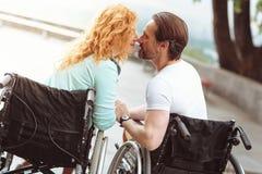 Romantisk make och fru i rullstolar som utomhus kysser royaltyfria bilder