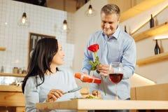 Romantisk man som ger rosen och gåva till hans kvinna Royaltyfri Bild