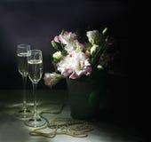Romantisk matställe med buketten av blommor, stearinljus och champagneexponeringsglas Arkivfoto