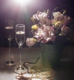 Romantisk matställe med buketten av blommor, stearinljus och champagneexponeringsglas Arkivbild