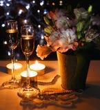 Romantisk matställe med buketten av blommor, stearinljus och champagneexponeringsglas Arkivfoton