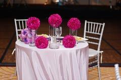 Romantisk matställe med vattenexponeringsglas och blommor Arkivfoto