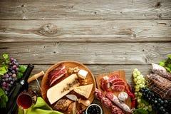 Romantisk matställe med vin, ost och traditionella korvar arkivfoto