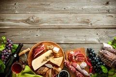 Romantisk matställe med vin, ost och traditionella korvar arkivfoton