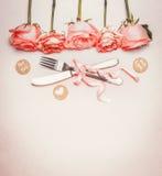 Romantisk matställebakgrund med tabellställeinställningen: rosor gränsar, bestick och bandet på pastellfärgad bakgrund, bästa sik Royaltyfria Bilder