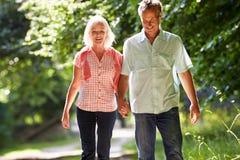 Romantisk mitt åldrades par som promenerar bygdbanan Fotografering för Bildbyråer