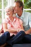 Romantisk mitt åldrades par som ser ut ur fönster Royaltyfri Bild