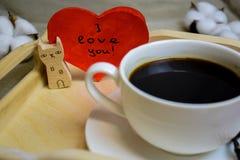 Romantisk morgon på valentin dag - kaffe i säng på ett trämagasin är en kopp kaffe och en kattställning med en vykort fotografering för bildbyråer