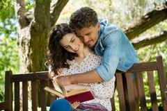 Romantisk parläsebok på bänk i trädgård arkivbild