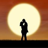 Romantisk parsilhouettekyss vid solnedgång Royaltyfria Bilder