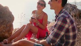 Romantisk picknick av att älska par med sjösida- och bergsikt på solnedgången