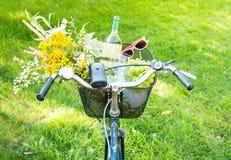 Romantisk picknick - blommor och vin i cykelkorg Arkivfoton