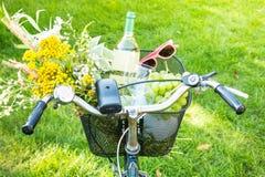 Romantisk picknick - blommor och vin i cykelkorg Arkivbild
