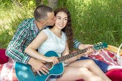 Romantisk picknick för sommar grabben visar flickan hur man spelar gitarren par gr?s att sitta arkivbild