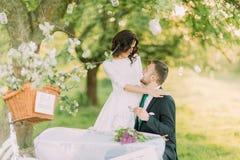 Romantisk picknick parkerar in Skämtsam brud som kramar hennes älskvärda nya make, medan han dricker te arkivbilder