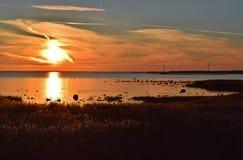 Romantisk pittoresk solnedgång i sjösidan med väderkvarnar Royaltyfri Bild