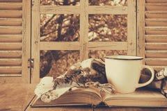 Romantisk plats av koppen kaffe bredvid den gamla boken framme av bygdsikten förutom det gamla lantliga fönstret Arkivbild