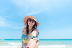 Romantisk plats av unga förälskelseparsemestrar i stranden Kvinna för hand för handmaninnehav, i att gå för klänning och för hatt fotografering för bildbyråer