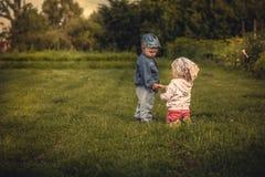 Romantisk plats med par av barn pojke och flickainnehavet med händer på solnedgången i det lantliga fältet som symboliserar föräl Royaltyfria Bilder