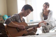 Romantisk pojke som spelar gitarren för hennes flickvän Arkivfoton