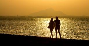 Romantisk promenad längs stranden på solnedgångpar Royaltyfri Foto