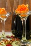 Romantisk sammansättning med den vinexponeringsglas, rosor och flaskan av vin arkivfoto