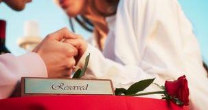 Romantisk sammansättning Reserverad och röd ros för platta på tabellen på den suddiga bakgrunden av de förälskade paren ömt stock video