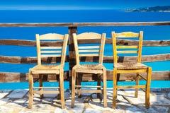 Romantisk sammansättning: tre stolar och djupblått hav Royaltyfria Bilder