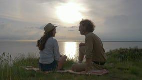 Romantisk semester, rolig skratta man och kvinna att meddela för att sitta på grönt gräs vid havet med skinande vatten på solnedg stock video