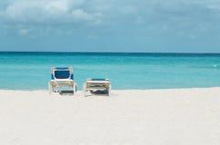Romantisk sikt av den karibiska stranden, två strandstolar mot blå himmel Royaltyfri Foto