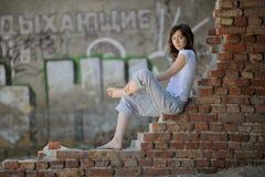 romantisk sittande vägg för tegelstenflicka Arkivfoton