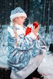 Romantisk snöjungfru i en festlig dräkt lilla flickan rymmer nytt års leksak och påse med gåvor glad vinterskog arkivbilder