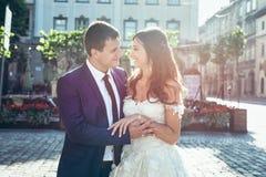 Romantisk solig stående Nätt precis gift är älskvärt le krama och rymma händer i gatan Arkivbilder