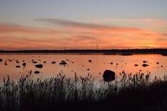 Romantisk solnedgång i sjösidan med väderkvarnar Royaltyfri Fotografi
