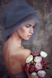 Romantisk stående av den unga damen i turban med ranunculusen Arkivbild