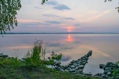 Romantisk stenskeppsdocka, gångbana i en sjö på en solnedgång, Uveldy, Uralsna, Ryssland Arkivbild