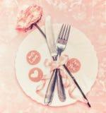 Romantisk tabellinställning med plattan, rosblomman, bestick och bandet på bakgrund för pastellfärgade rosa färger Arkivfoto