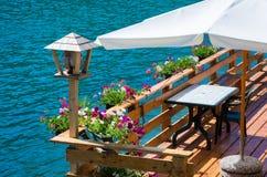 Romantisk terrass på sjön Alleghe, Belluno, Italien: en fascinerande sjö, i den geografiska hjärtan av DolomitesUNESCOvärlden Nat Royaltyfri Foto