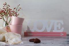 Romantisk valentindagbakgrund Två rosa koppar för te och ordförälskelse på ljus bakgrund fotografering för bildbyråer