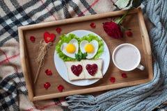 Romantisk valentindagfrukost i säng med hjärta-format ägg, rostade bröd, driftstopp, kaffe, rosa och kronblad royaltyfria bilder