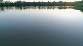 Romantisk vattentur på den rena sjön i afton på aftonrodnad lager videofilmer