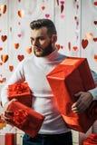 romantisk ?verrrakning G?va f?r flickv?n Attraktivt macho med g?vor firar valentindag Sexig skäggig röd grabbhåll arkivbilder