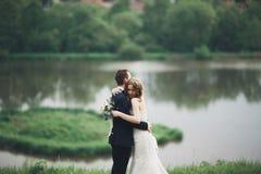Romantiska brölloppar, man och fru som poserar nära den härliga sjön arkivbild