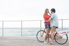Romantiska Caucasian par som är pinsamma på cirkulering på stranden arkivfoton