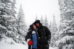Romantiska fotvandra par som omfamnar i vinterbergen Arkivbild