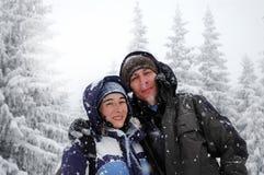 Romantiska fotvandra par som omfamnar i vinterbergen Arkivfoton