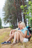 Romantiska fotvandra par som ser bort, medan koppla av i skog Fotografering för Bildbyråer