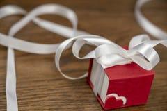 Romantiska gåvor i heder av valentin dag, röda hjärta och fall royaltyfria bilder